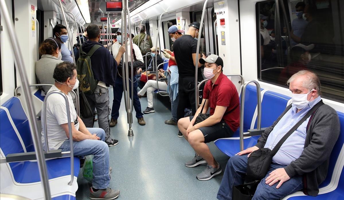 Pasajeros protegidos con mascarillas en un convoy de la línea 4 del metro de Barcelona