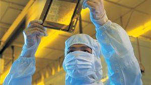 Trabajador de TSMC revisa una de las obleas producidas en la factoría taiwanesa.