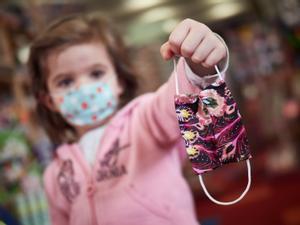 Una niña sujeta una mascarilla infantil