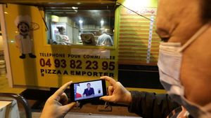 Un hombre mira el discurso de Macron a través de su móvil junto a un local que vende pizzas para llevar.