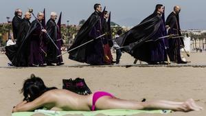 Bañistas y participantes en una procesión de Semana Santa, en la playa de Valencia.