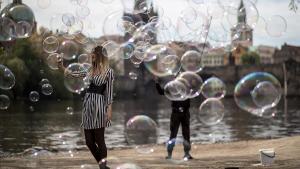 Una chica se hace un selfi rodeada de las burbujas que hace flotar en el aire un artista callejero a orillas del río Moldava, este viernes, en Praga, República Checa.