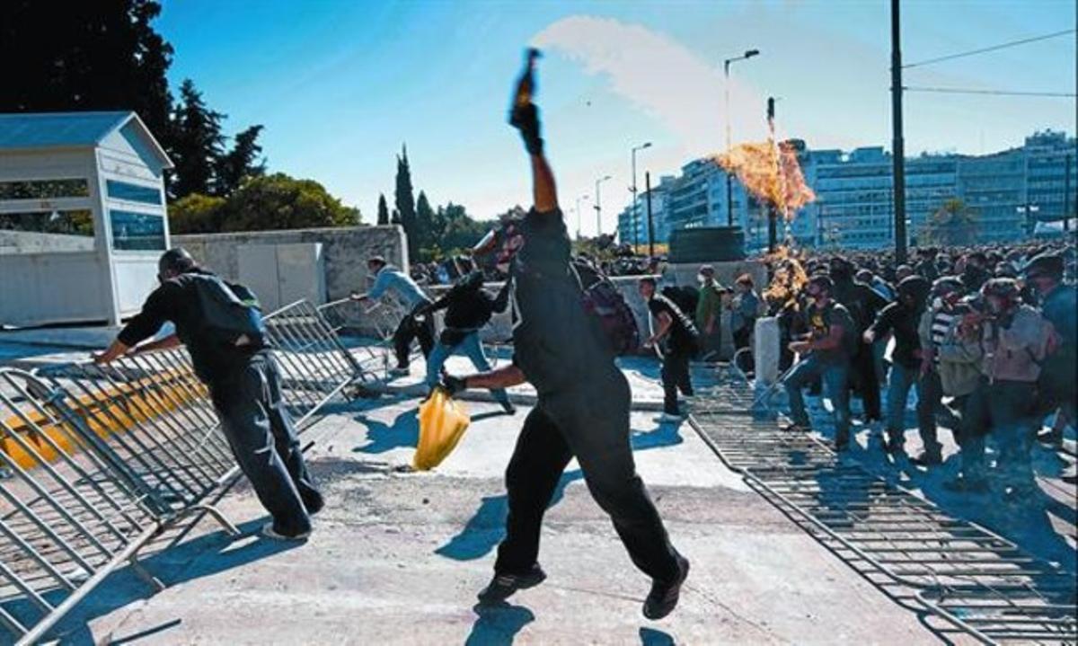 Un activista lanza un coctel molotov al final de la manifestaciónde Atenas, ayer.