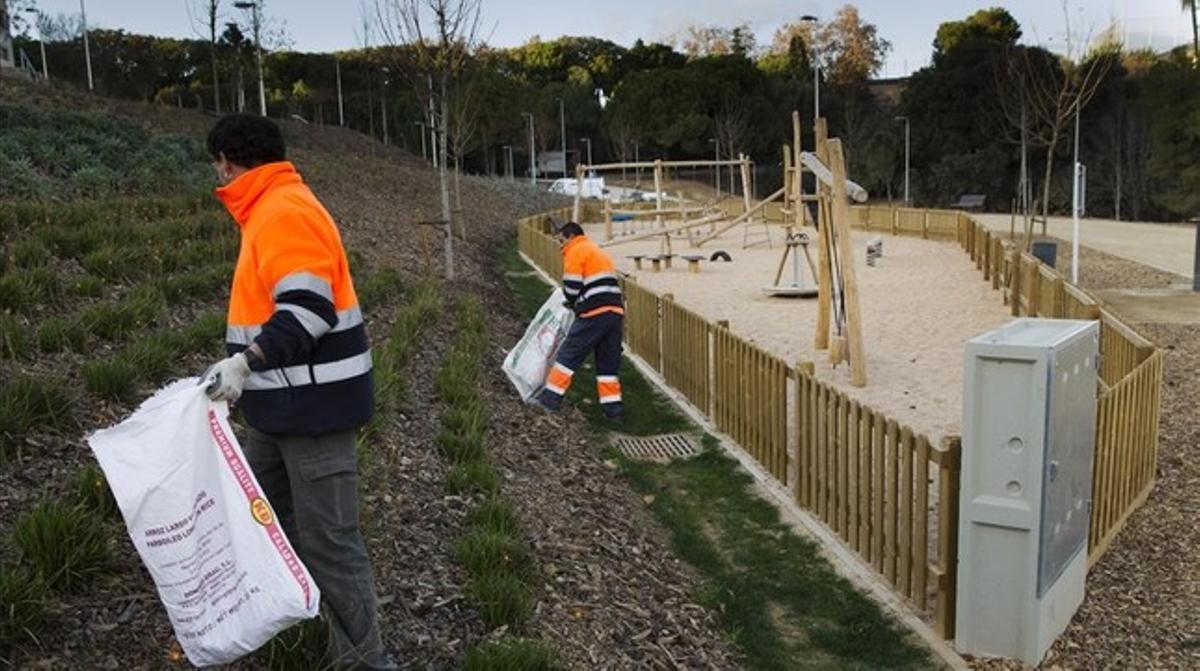 Dos operarios terminan la limpieza tras la terminación delas obras del parque de Can Boixeres, este viernes.