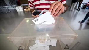 Un elector deposita su voto en la urna en unas elecciones catalanas.