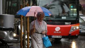 Una mujer camina bajo la lluvia con gabardina y paraguas, en Barcelona.
