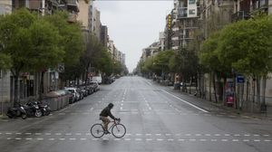 Un ciclista solitario cruza la desierta calle de Aragó.
