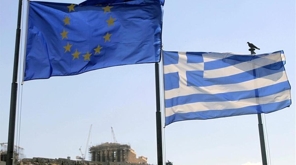Una bandera griega y una de la UE ondean junto a la Acrópolis (al fondo), en Atenas, este martes.