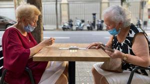 El impacto de la Covid-19 en la población: baja la esperanza de vida y la migración. En la foto, dos mujeres juegan a cartas en la calle, en Barcelona.