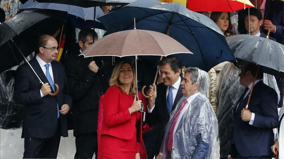 Miguel Ángel Revilla, con chubasquero, junto a Susana Díaz y Javier Fernández en el desfile del día de la Hispanidad.