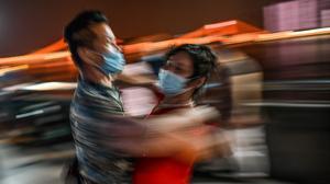 Una pareja baila con mascarillas en un parque junto al río Yangtsé,en Wuhan, localidad china donde se originó el coronavirus, el 27 de mayo.