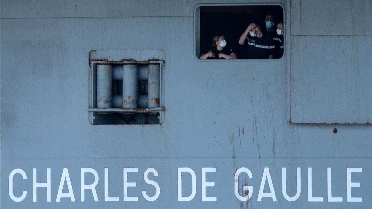Unos marineros del 'Charles de Gaulle' con mascarillas se asoman por una ventana del portaaviones.