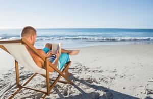 Un hombre leyendo un libro en la playa.