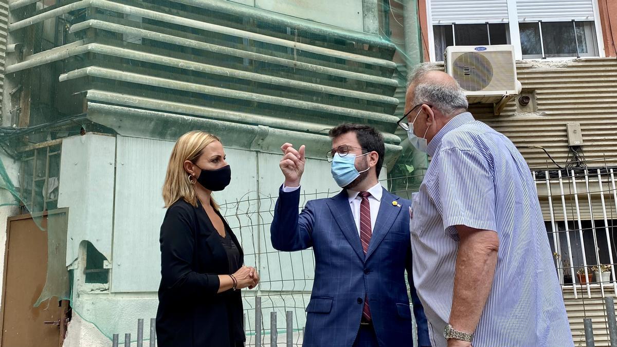 Aragonés, junto a la alcaldesa de Badia y un vecino del municipio, ante un edificio repleto de láminas de amianto