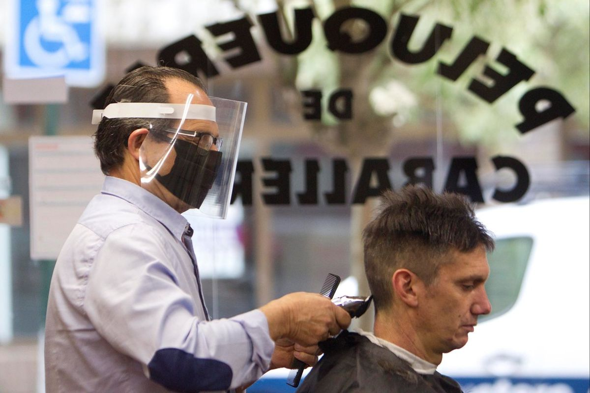 Un peluquero, con un cliente en su establecimiento.