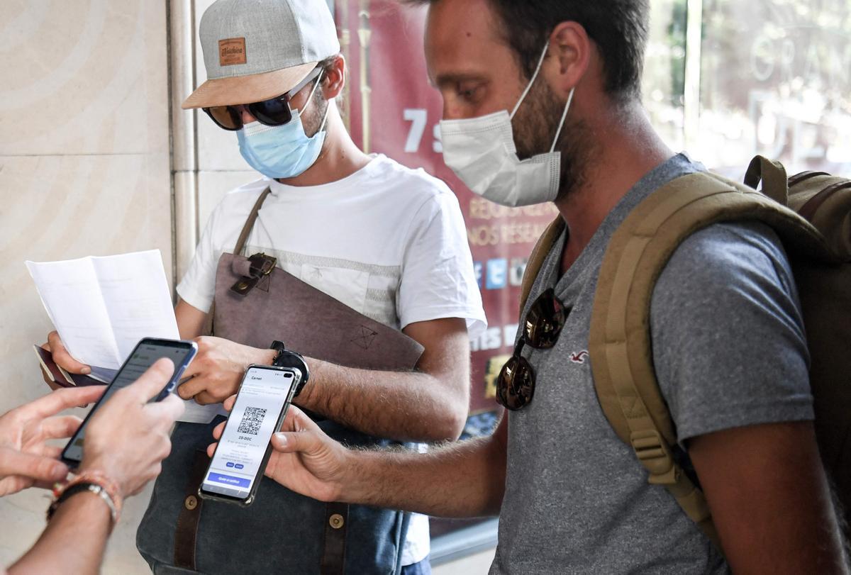 Dos hombres muestran su pasaporte sanitario a la entrada a un cine de Paris.
