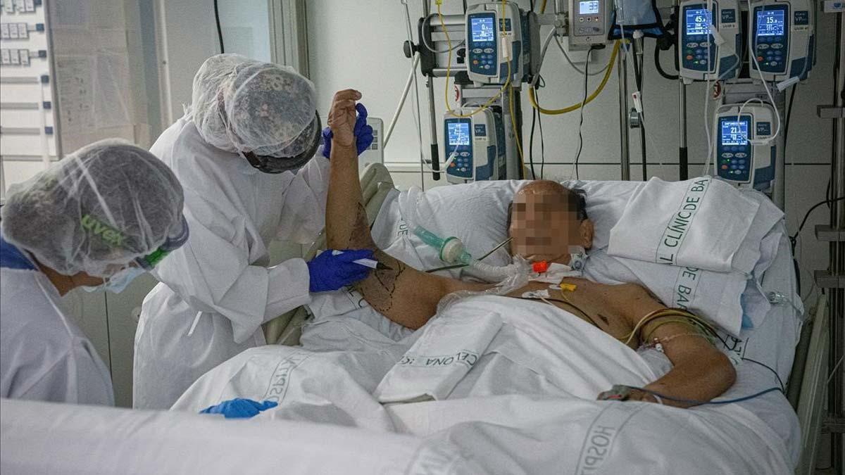 El coronavirus deja 17.000 casos diarios en una España en estado de alarma. En la foto, un paciente con covid en la UCI del Hospital Clínic de Barcelona.