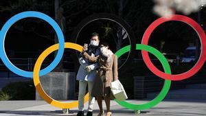 Una pareja de turistas se saca una foto junto a los aros olímpicos instalados en Tokio.