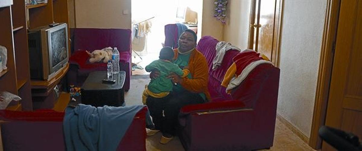 Perpetua Obi y su hijo, el jueves, en su piso de Santa Coloma de Gramenet, aguardando el desahucio que a última hora fue aplazado.