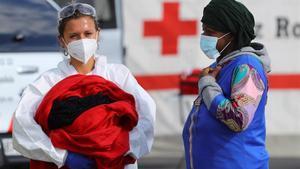 La bebé nacida en plena travesía, en brazos de una sanitaria y junto a su madre, en el puerto grancanario de Arguineguin.