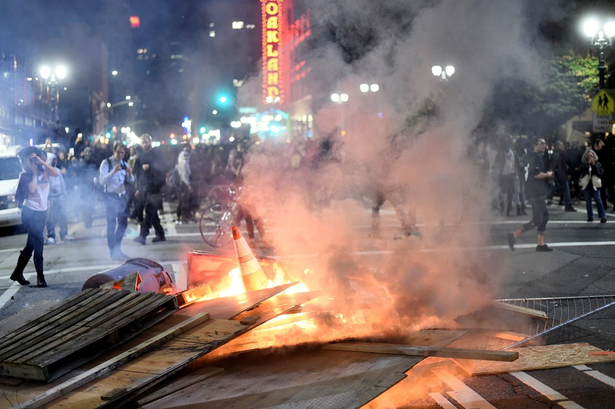 Mobiliario urbano en llamas durante la protesta contra Trump en Oakland.