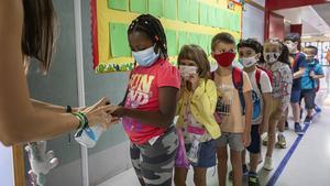 Un grupo de niños hacen cola para desinfectarse las manos antes de entrar en clase, en un colegio de Benimaclet (València), este lunes 7 de septiembre.