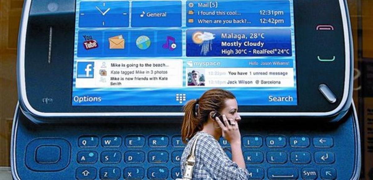 Una ciudadana londinense pasa ante un anuncio de un teléfono inteligente de Nokia.