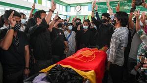La gente muestra un saludo con tres dedosen el funeral de un estudiante de medicina de 19 años que fue abatido durante la represión contra los manifestantes.