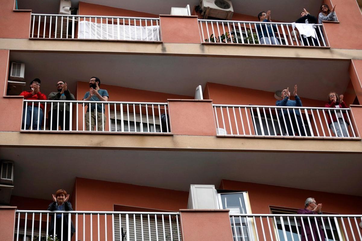 Vecinos de L'Hospitalet de Llobregat salen a sus balcones y ventanasa aplaudira los sanitarios, el pasado 29 de marzo.
