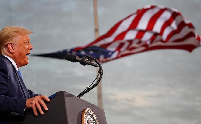 Donald Trump habla, con una bandera detrás de él, durante un acto de campaña en el aeropuerto de Cecil, en Jacksonville, Florida, el 24 de septiembre del 2020.