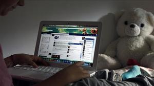 Unniño navega por internet en su habitación.