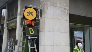 Un operario cambia el logotipo de Bankia por el de CaixaBank en la oficina del número 116 de la Rambla del Poblenou de Barcelona.