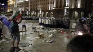 Manifestantes lanzan botellas contra la policía durante una protesta en Sofia.