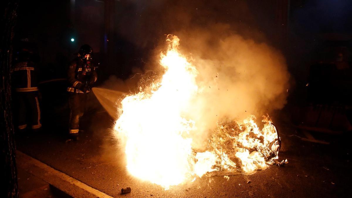 Los bomberos apagan los contenedores que los manifestantes han quemado en la Via Augusta de Barcelona este martes