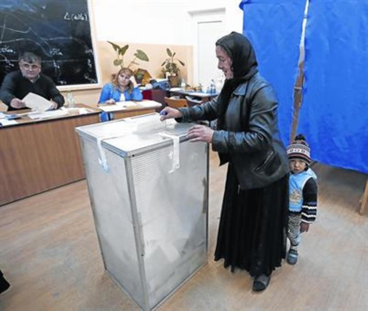 Una mujer deposita su voto en Sintesti, cerca de Bucarest, ayer.