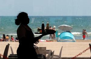 Una camarera lleva bandeja con bebidas en un restaurante de la Malvarrosa