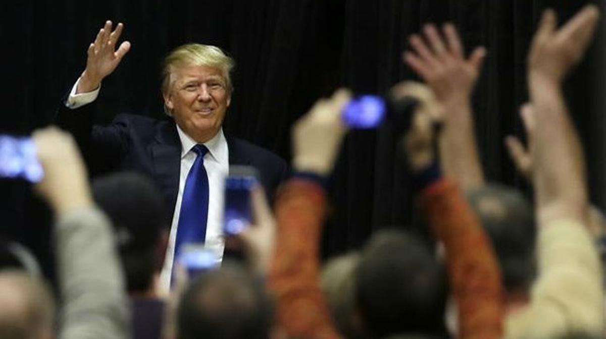 Trump saluda a sus seguidores al llegar a un acto de campaña en la Clinton Middle School, el 30 de enero, en Clinton (Iowa).