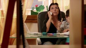Una mujer habla por teléfono mientras sostiene a su hijo, en una imagen de archivo