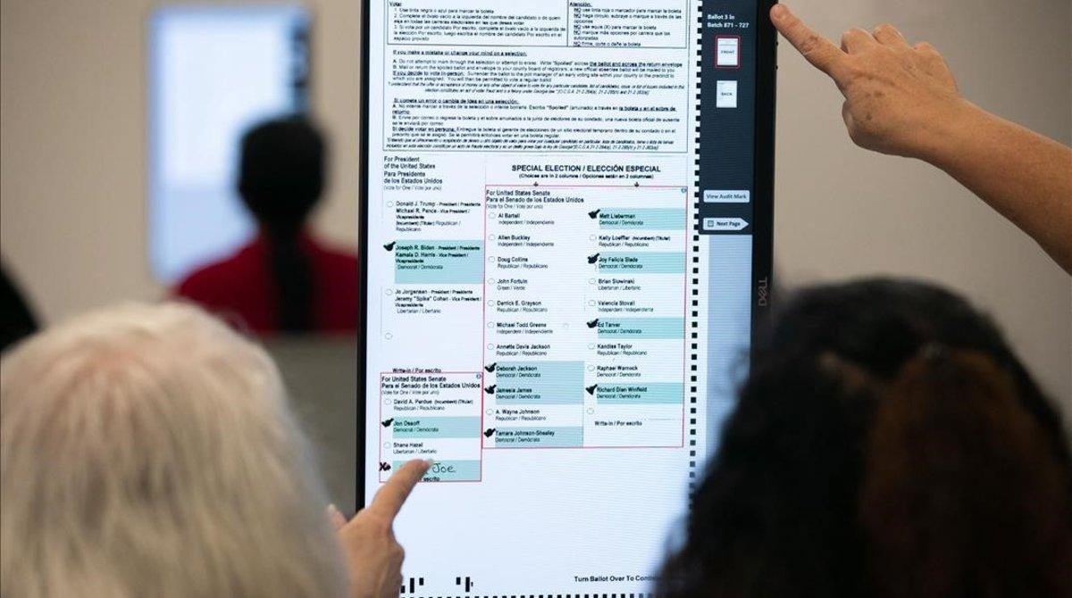 Varios miembros de uncolegio electoral de Georgia miran un panel.