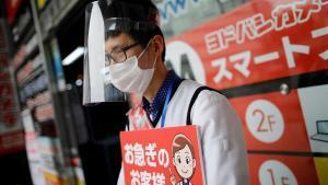Un empleado de una tienda de electrónica usa mascarilla protectora en una calle de Tokio.
