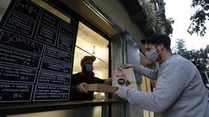 Un cliente compra comida para llevar en un establecimiento de Barcelona.