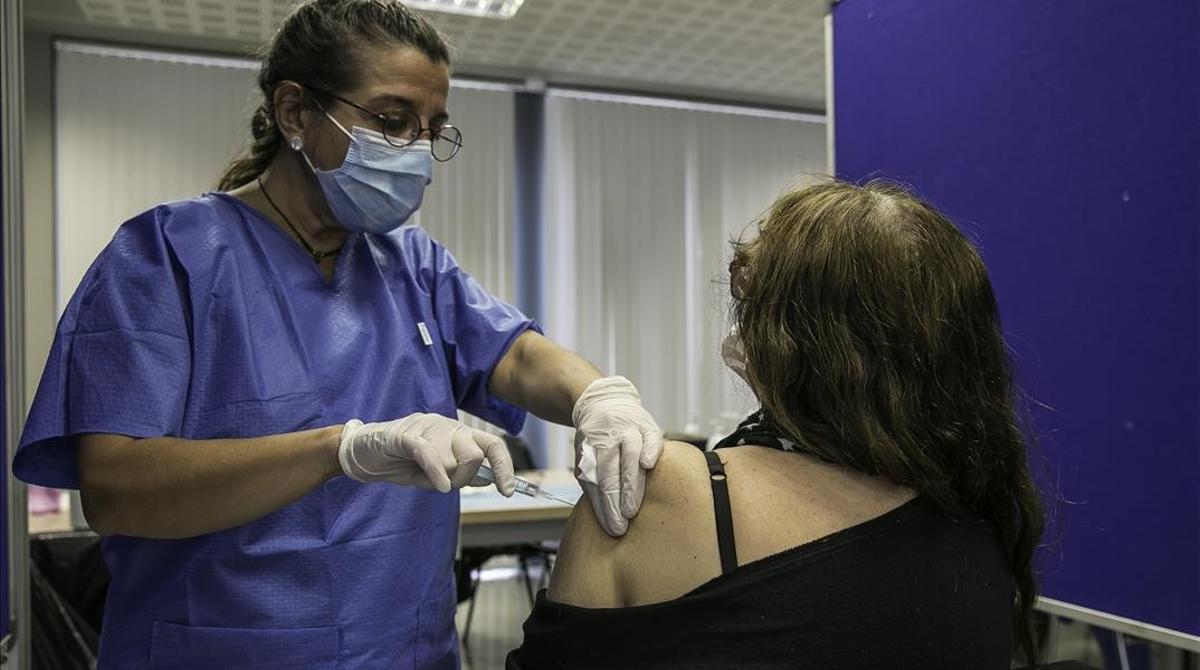 Una mujer recibe la vacuna de AstraZeneca en el centro de vacunación instalado en la facultad de Geografía e Historia de la UB.