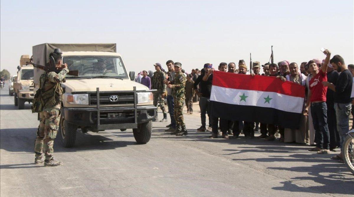 Vecinos de la aldea de Ghebeshdan la bienvenida a las tropas sirias.