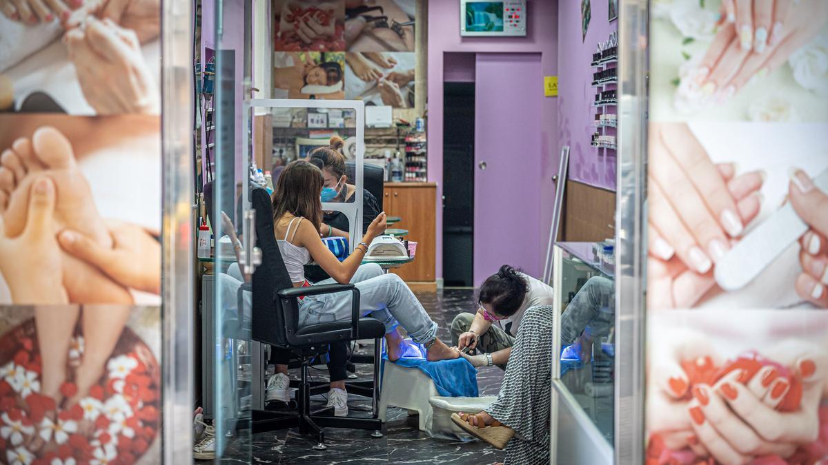 Trabajadoras estéticas de origen asiático atienden a una joven española en Barcelona.