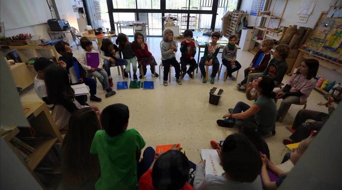 Unos alumnos escuchan la explicación desu maestra en el colegio público Els Encants de Barcelona.