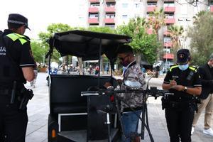 Dos agentes de la Guardia Urbana revisan los papeles de un conductor de bicitaxi.