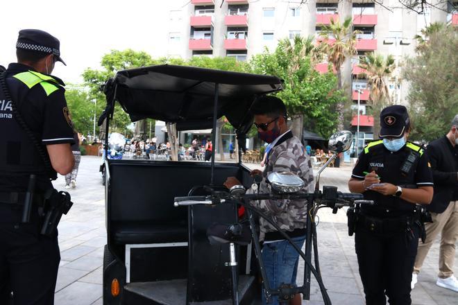 Dos agentes de la Guardia Urbana revisan los papeles de un conductor de bicitaxi