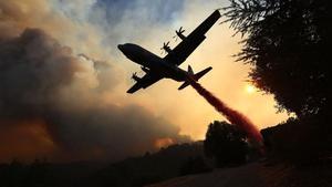 Un avión intenta contener las llamas en California.