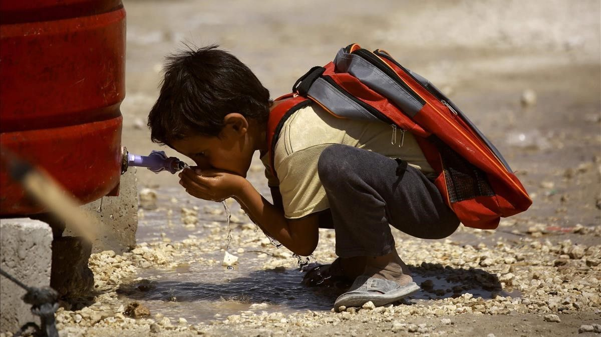 Un niño sirio, desplazado por la violencia del Estado Islámico, bebe agua antes de empezar el primer día de escuela en un campo para desplazados internos en Ain Issa, Siria.