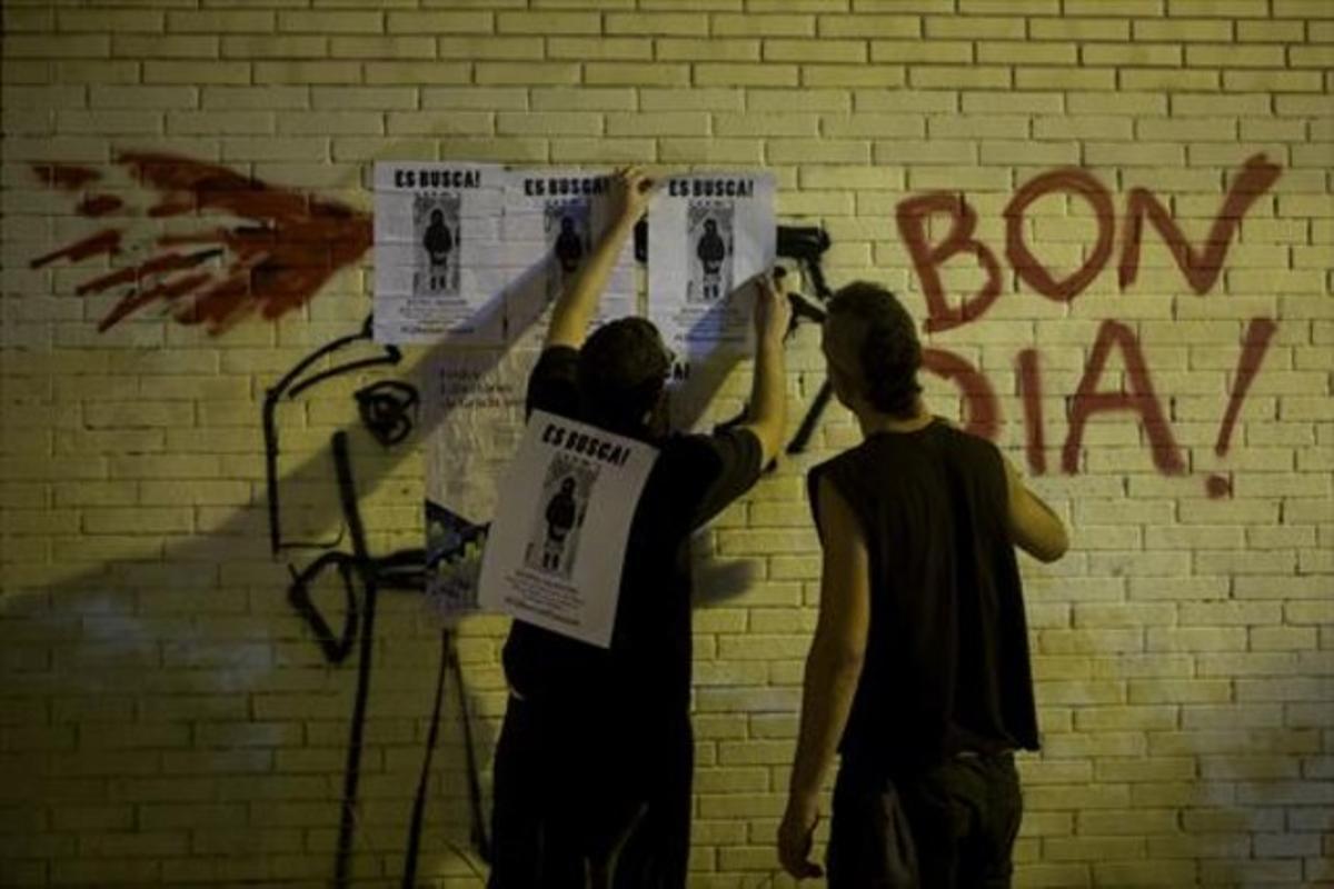 Dos chicos cuelgan carteles denunciando la retirada por parte de los Mossos del decorado de las fiestas.